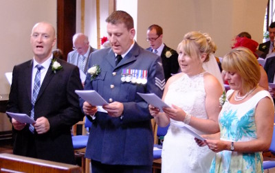 The Best Man, Groom, Bride and Best Woman sing a hymn